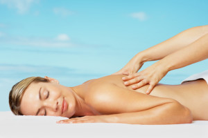 Portrait of a smiling relaxed woman receiving a back massage against blue sky